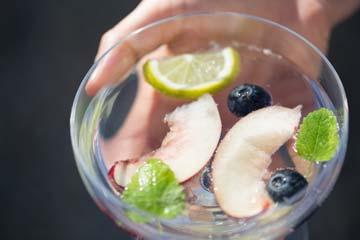 Glas mit Obststücken, Beeren und Minzeblättern in klarer Flüssigkeit
