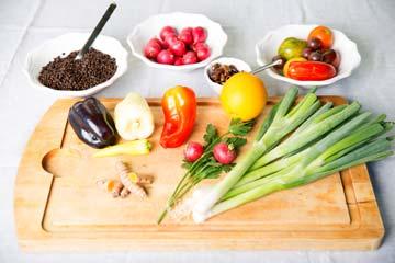 Jungzwiebel, verschiedene Paprika, Tomaten, Linsen, Radieschen, Oliven, Kurkuma und Kräuter auf einem Schneidbrett und in kleinen Schalen