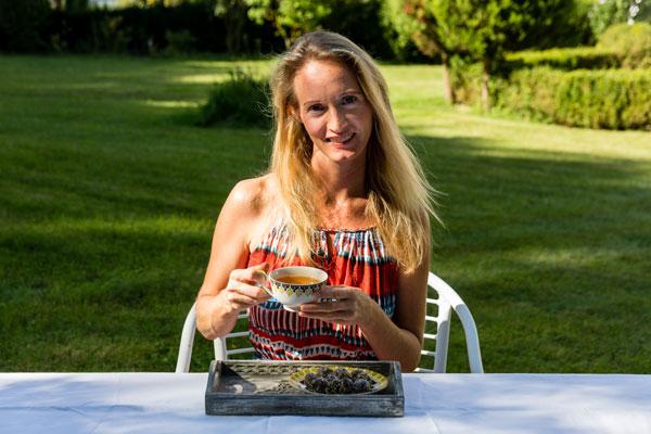 Portrait Rose Sachslehner in einem Garten, mit Tee und Früchtekugeln